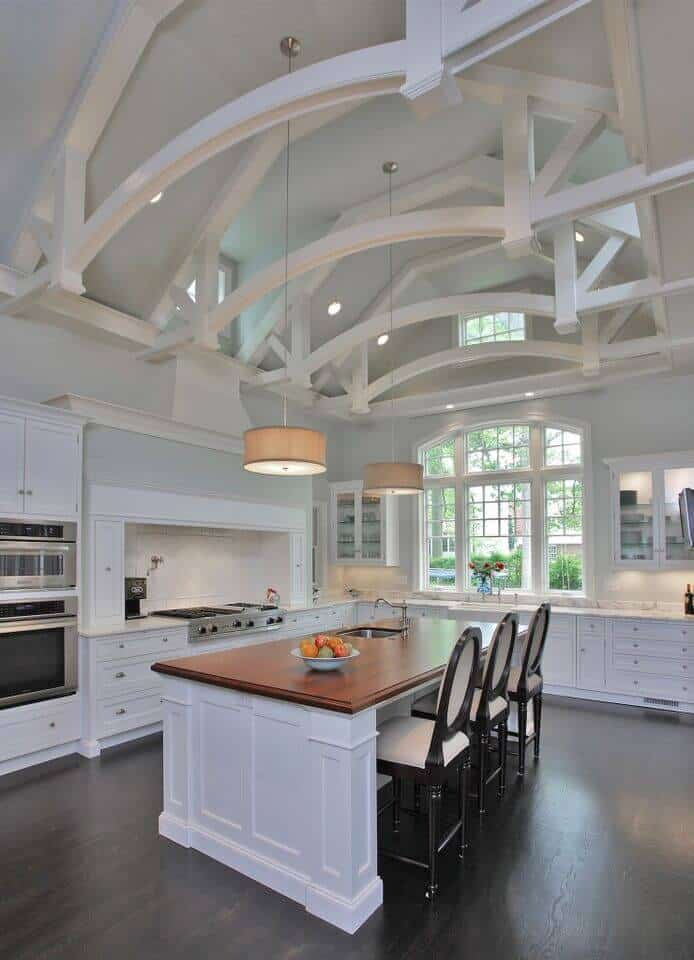 This kitchen has decent size for a simple island. It also has a high ceiling, making the room appear more spacious. It has the right combination of white L-shape kitchen counter, wood table top, and orange circular hanging lights.