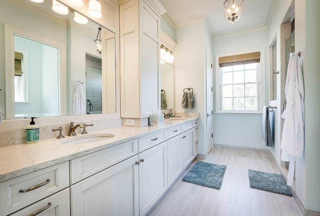 This large bathroom features a lovely double-sink counter for individual use. The blue floor rugs and towel give a pop of color in this all-white interior, including the lightings, counter, and shelves. The large mirrors are perfect for this spacious bathroom, while the window at the end of the room allows for a quick view outside.