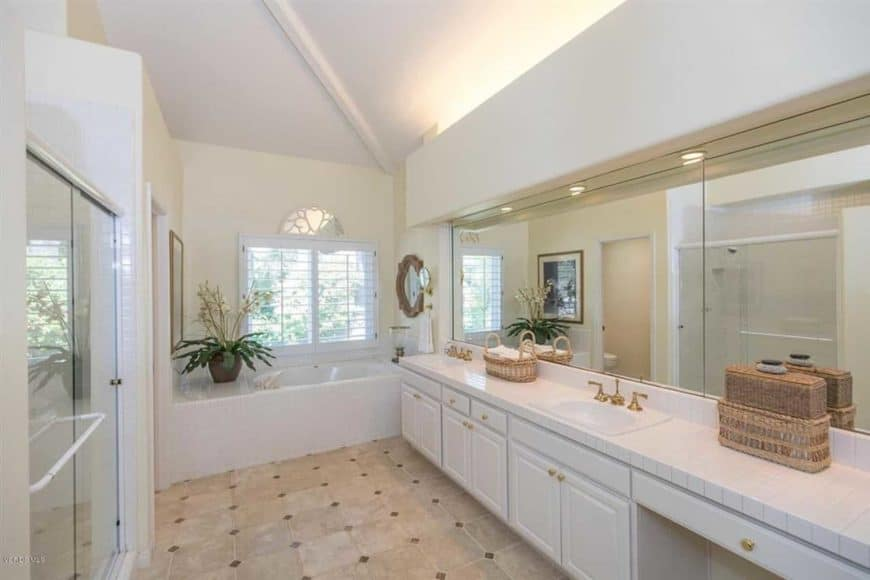 This white bathroom featuring white walls and a white ceiling. This room also has a large mirror and a wooden cabinet under the basin sink.