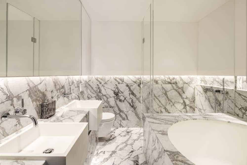 The white primary bathroom has a white double sink match with contemporary countertops and elongated bathtub.