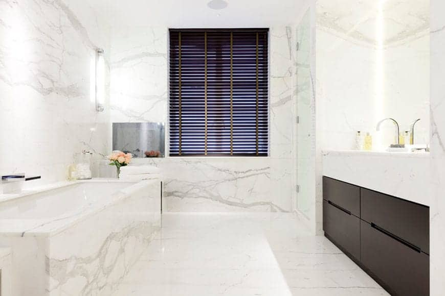 The white primary bathroom features marble vanities on both sides. Primary bath has the sophistication and detail that only show up in the most luxurious of dwellings.