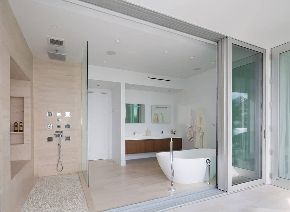 A white and brown style wall mounted waterfall shower head combines with the handheld showerhead and glass paneling to make this the ultimate place to freshen up. It also has vintage-looking bathtub.