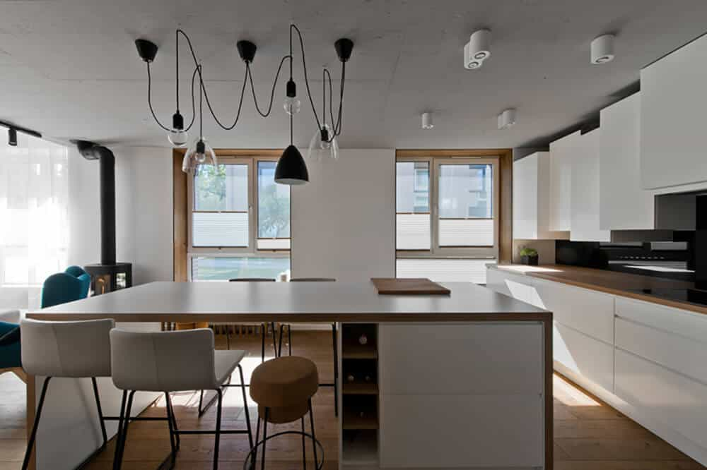 For more Asian kitchen inspiration, take some pointers from this design with its simplistic white and wooden kitchen counter and dining table. Its wide glass windows provide a beautiful sunray during the day, which is also great for cutting power cost short. This kitchen has a good mix of pendant lighting and recessed lights.