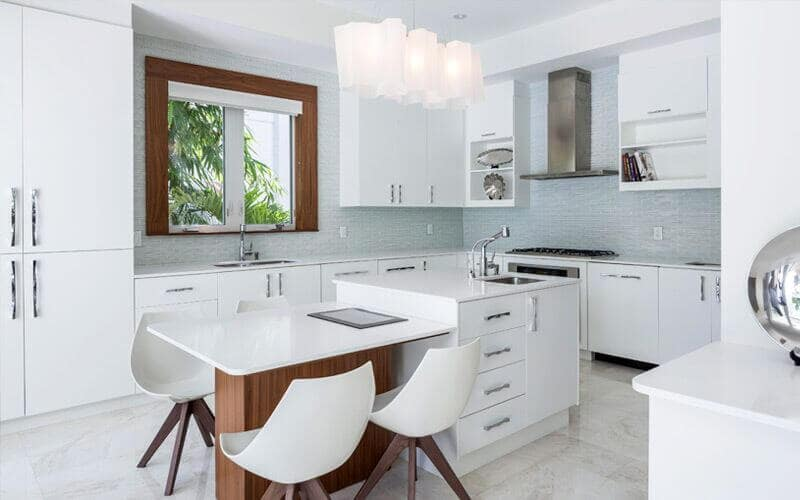 For a modern take, this kitchen has a combination of white, wood, and blue aesthetics. You got white drawers, shelves, kitchen bar with sink, and dining tabletop and chairs, while the walls have a dainty blue pattern. With wooden accents, a glass window, and white rectangular pedestal lights, this kitchen looks good for any tiny space.