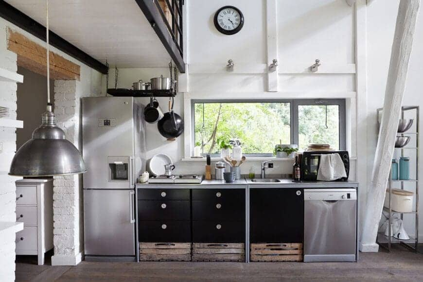 This kitchen showcases the perfect combination of rustic and industrial with its steel appliances and matte black drawers. The wooden crates and hard flooring add texture to the whole kitchen, while the white walls and panels add a nice contrast for a soft touch.