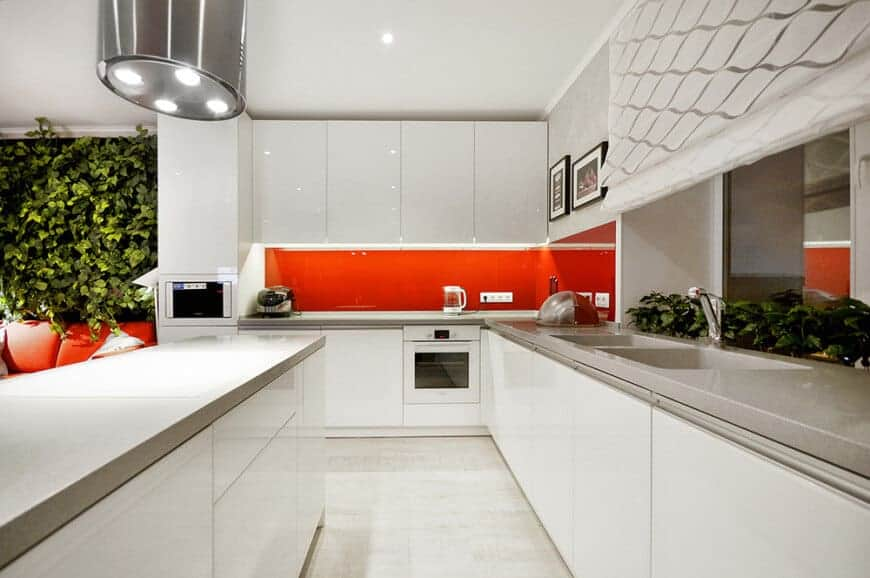 Sleek, urban, and eclectic - these must be the perfect words to describe this contemporary kitchen. It has white counters with a grey top, and a bright red splashback for that pop of color, making it both fashionable and refined.