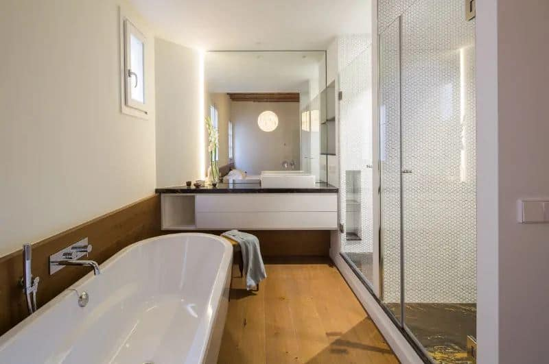 Small bathroom with freestanding bathtub on the hardwood flooring and dark countertop with a basin sink. This bathroom boasts a walk-in shower and it has mirrors that mounted on the white walls.