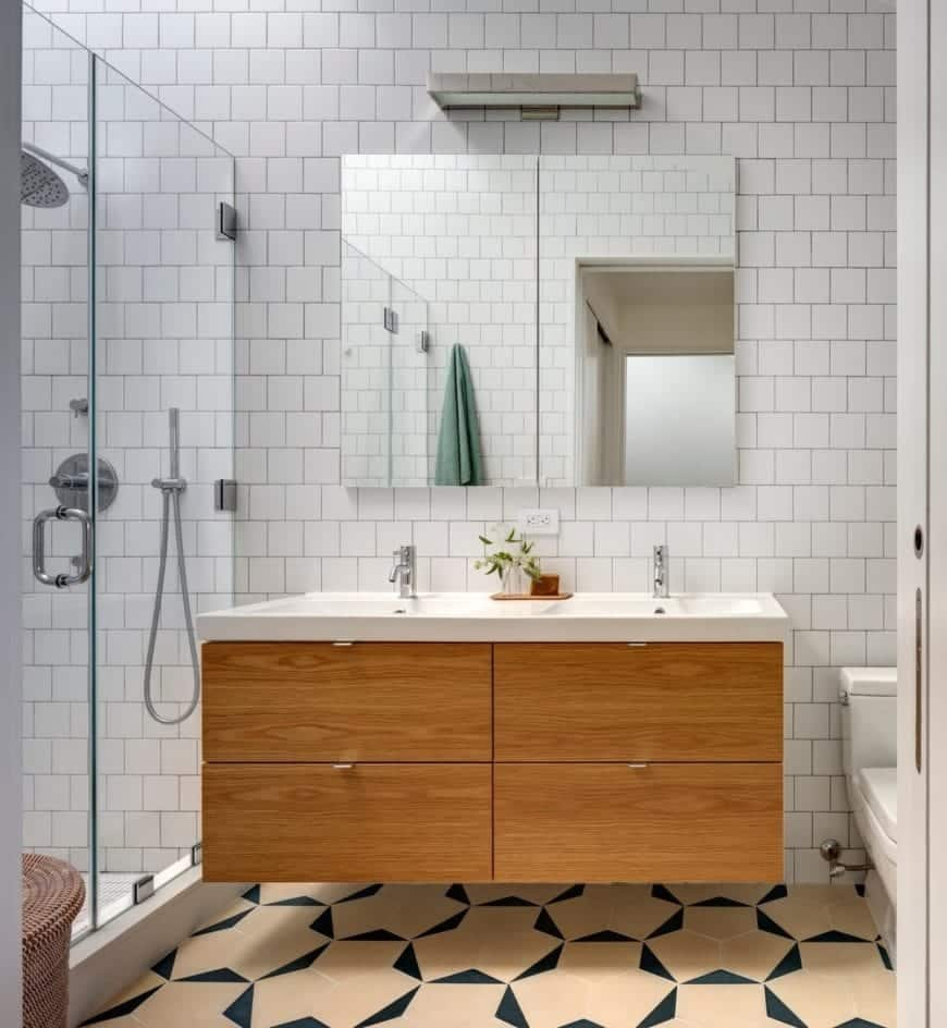 Wooden cabinetry under the raised sink basin gives this bathroom a contemporary feel. This bathroom also has a glass paneling enclosed shower and a classy marble flooring.