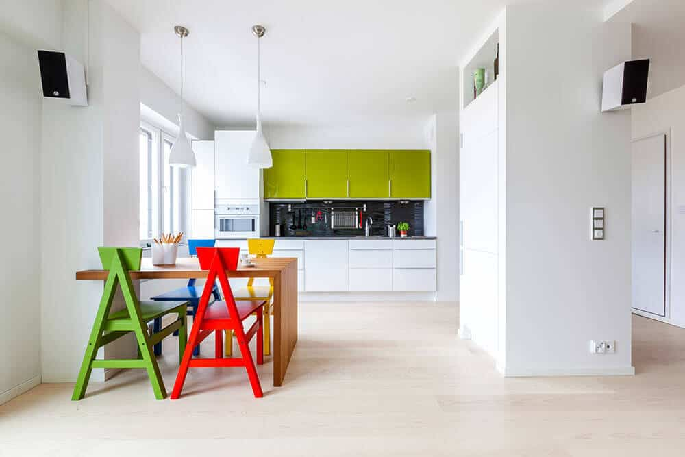 This chic kitchen has a playful touch to it with its colorful dining set and bright green cupboard, which is a good contrast to the white drawers, pendant lights, and the large pantry in the middle of the kitchen.