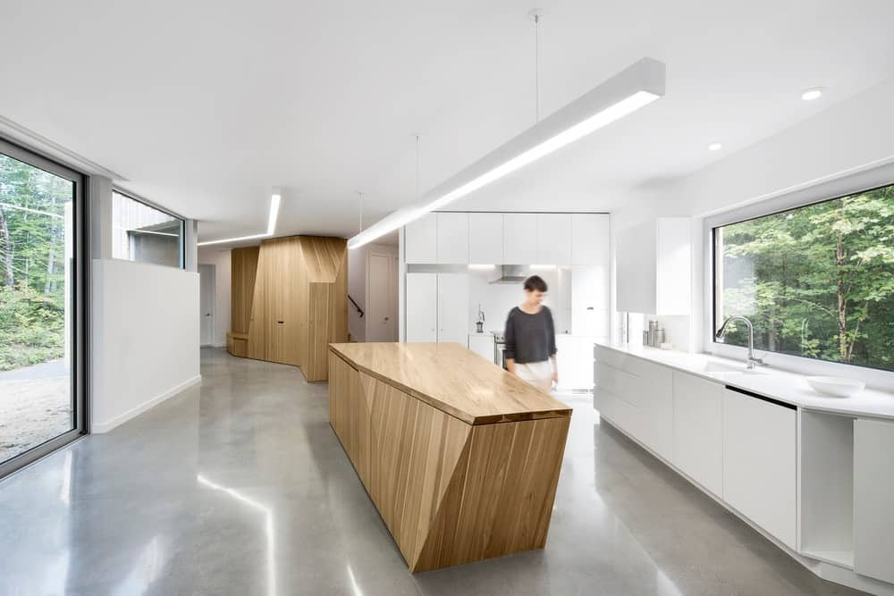 Going for a minimalist kitchen design? Go for something with neutral colors like this all-white kitchen with its grey flooring and wooden island and cabinet. The glass window and door also leave a simplistic design for a more refreshing take.