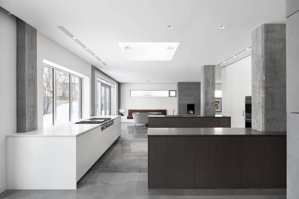 This chic minimalist kitchen features a sleek counter with a fuss-free stovetop, dark brown dining bars with grey pillars, and smooth grey marble flooring as well. It has recessed lights on the ceiling for better light distribution, and glass windows and doors for a nice outdoor view.