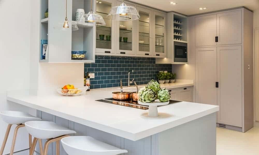 This Spanish style kitchen has a nice blue-green splashback that complements the white L-shape countertop, mirrored shelves, and translucent pendant lights.