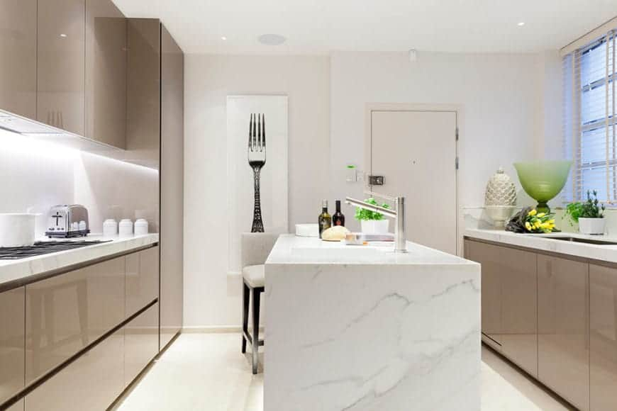 This minimalist kitchen has a marble designed peninsula, which goes well with the tan drawers on the sides. The wall lights provide ample lighting by the sink. For a personal touch, the kitchen has a tasteful fork art on the wall.