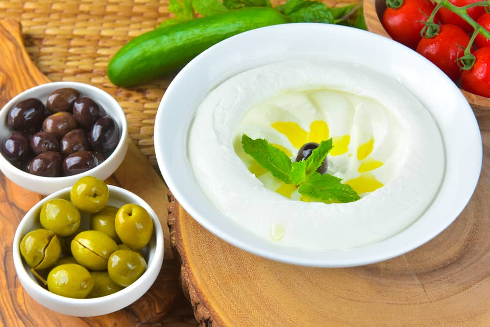 A very appetizing bowl of labneh garnished with mint and olives.