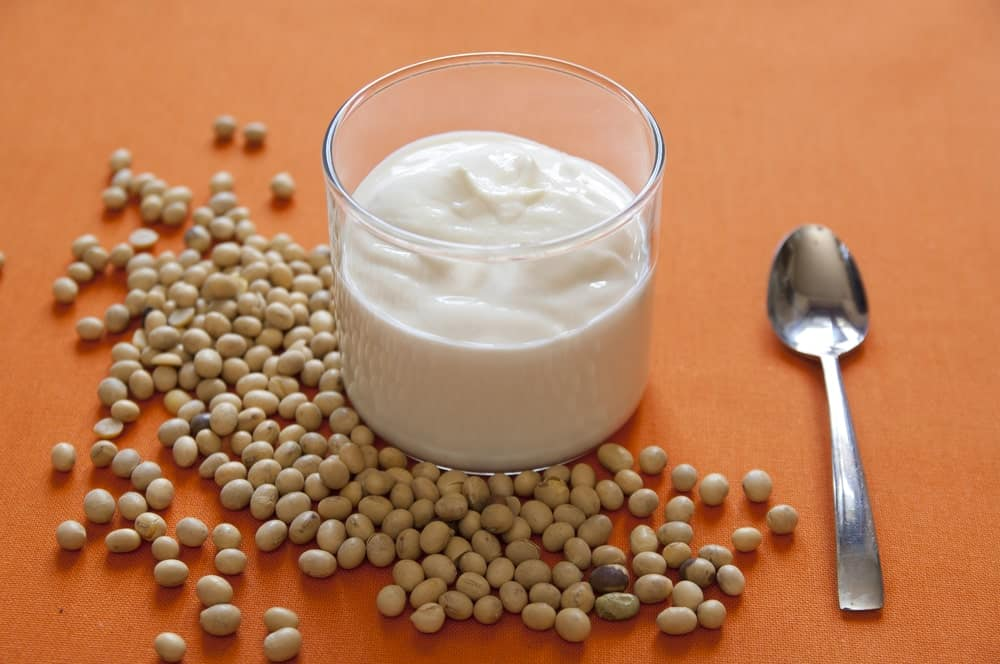 A close-up look at a glass of soy yogurt decorated with soy beans.