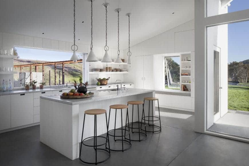 This Scandinavian style kitchen offers a refreshing vibe for your guests with its all-white interior including the island, triangular pendant lighting, door frame, walls, and drawers. There are also plenty of shelves for plates and utensils, a set of rustic-industrial bar stools, and glass windows that welcome a relaxing view from outdoors.