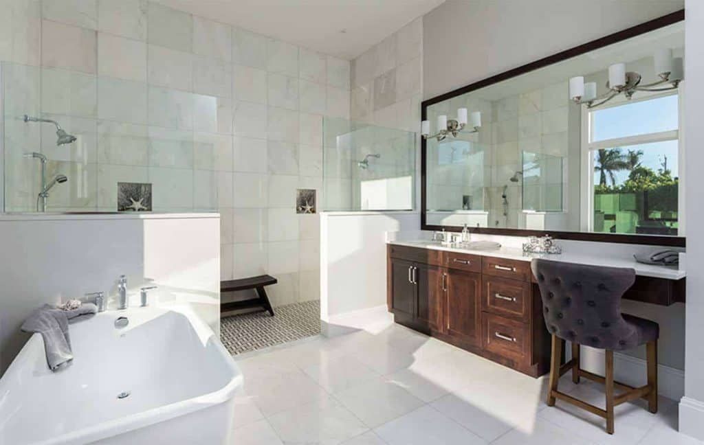 For a more contemporary take, this bathroom shows a mix of white and brown with the white tile flooring and the bathtub while you would immediately notice the brown accent on the vanity drawer which also comes ready with a cushioned chair. The mirror's frame also matches the brown accents of the bathroom. With a walk-in shower area with a resting chair and a bathtub in the open space, you can be sure this bathroom is versatile on its own.