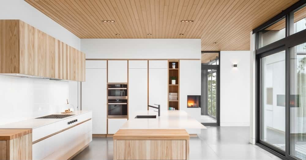 For an Asian inspired kitchen, take inspiration from this style. It shows a fine and simplistic design for fuss-free cooking. It features plain white shelves with wooden partitions, as well as a wooden aesthetics for the pantry and the additional drawers beside the kitchen counters, that also play out as sidebars.