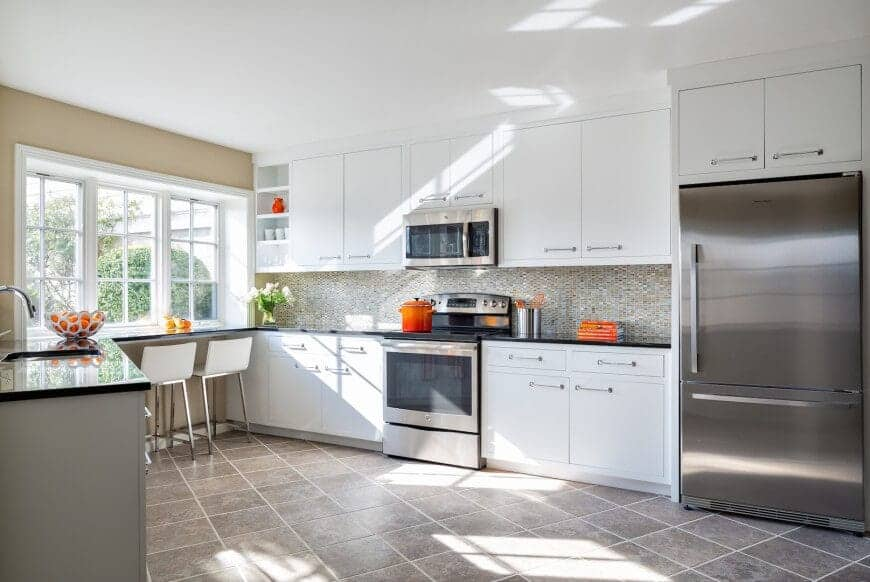 This kitchen has a modern Asian style with its tiled flooring, white counters, and steel fridge. Right by the window pane is the breakfast nook where one can enjoy the sunlight and the view while having a nice meal. The fresh flowers give a lovely finish to the whole kitchen.