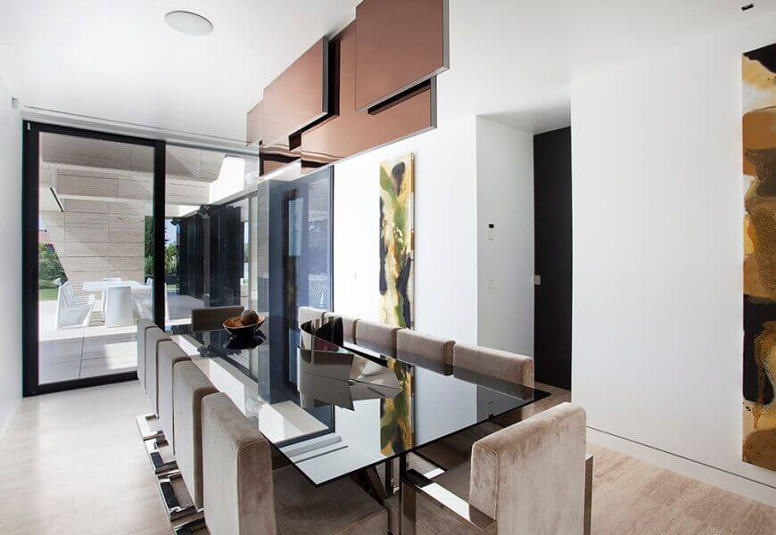 The modern house featuring a glass dining table set with modern chairs. This room also has white walls and great wall decors.