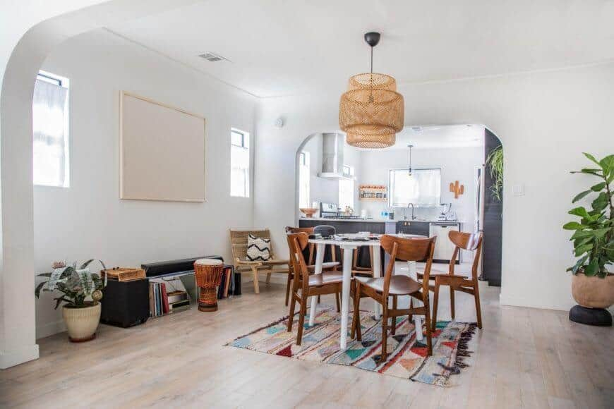 A dine-in kitchen featuring hardwood flooring and a small round table with wooden chairs on the rug. This room also has a white wall and a white ceiling with gorgeous hanging lights.