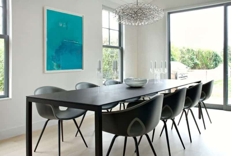 Full view of dark wooden tables with modern chairs brightens up by stunning chandelier. This room has a glass sliding door leading to the garden.