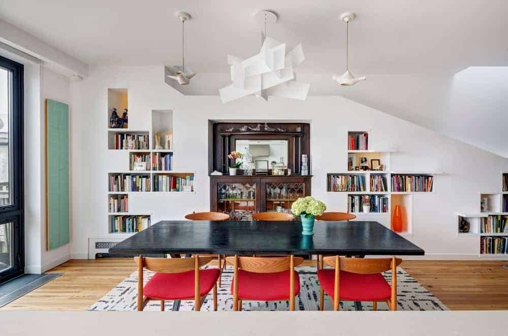Modern dining area and wooden dark table along with wooden chairs on the rug. This room highlighting a white wall and bookshelf.