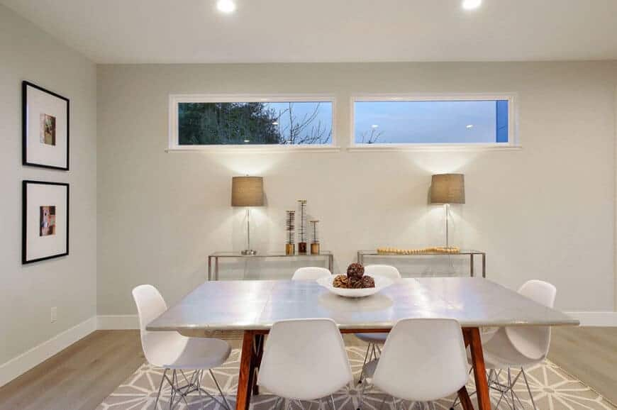 A dining room with a modern table and chairs on the rug. This room features a grey wall with great wall decors lightens up by a pair of a table lamps.