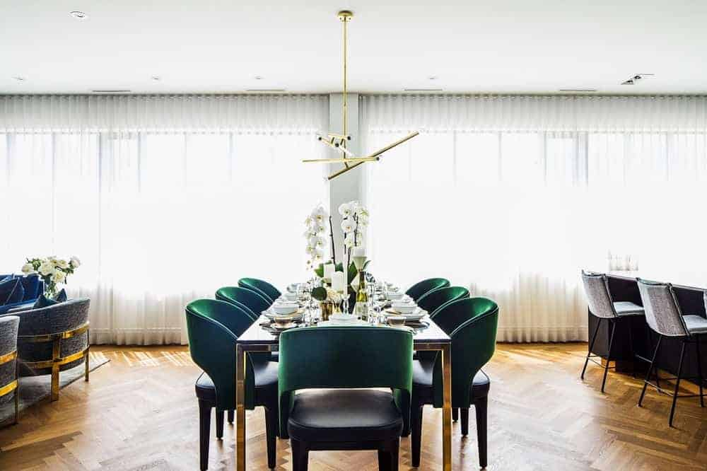 The dining room boasts an elegant theme featuring multiple glass windows blending with the white walls and hardwood flooring along with green seats.