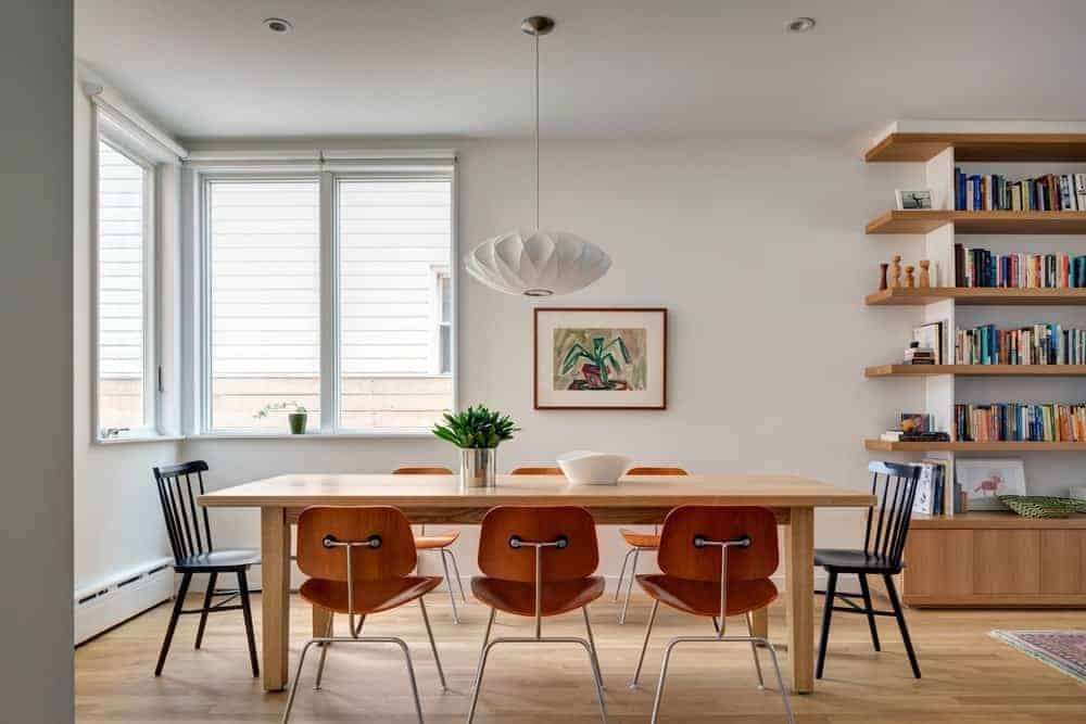 Full view of the wooden dining tables and chairs lighten up by pendant light. This room features hardwood flooring and a glass window.