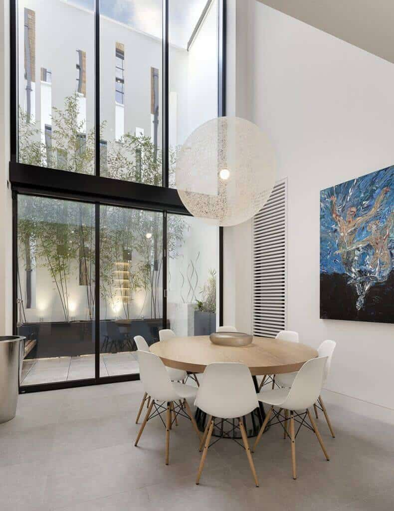 A stylish home with a wooden round table set surrounded by white walls with art design and a huge window with a pleasant view of the garden.