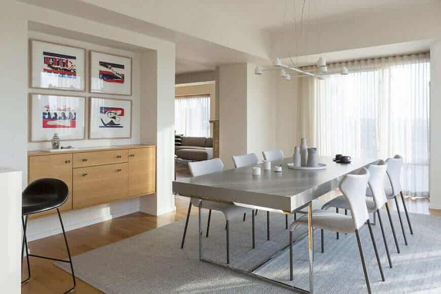 Dining area highlighting stylish tables and chairs on the rug. This room also showing hardwood flooring and a white wall with gorgeous interior design.