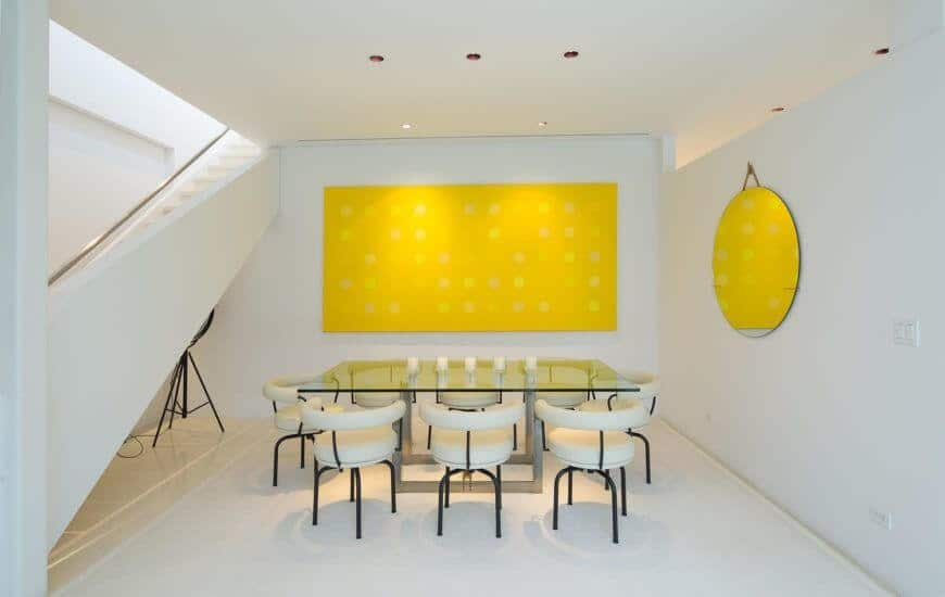 White modern dining room featuring glass tables and stylish chairs. It also features white walls and huge wall decor.