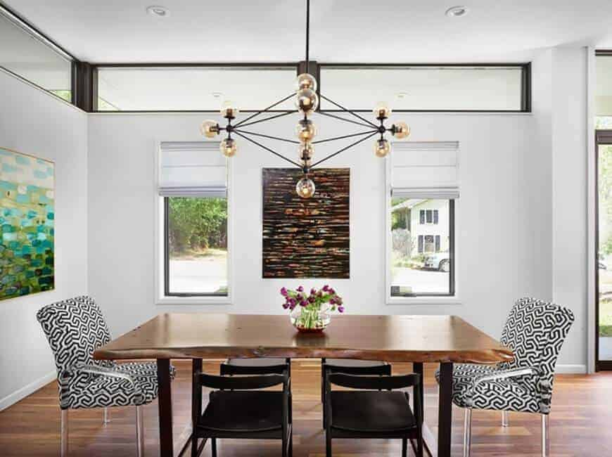 Small white dining area highlighting hardwood flooring and wooden tables with a pair of modern chairs light up by chandelier. There's a window with a view outside the house.
