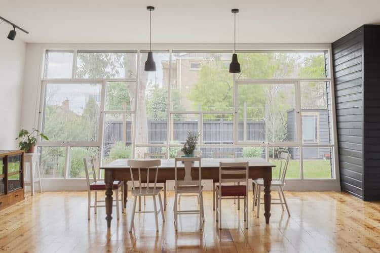 Small dining room featuring hardwood flooring and wooden tables with wooden chairs light up by hanging lights. This room also features a large window with a pleasant view outside.