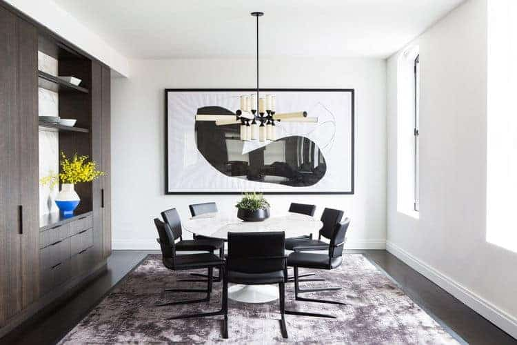 Modern dining area with round table pair with black chairs brightens by an impressive chandelier. This room has white walls and huge art.