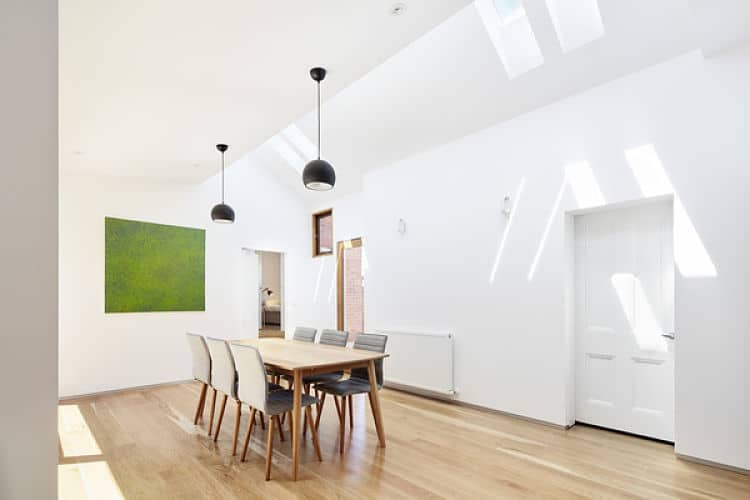 White dining area featuring white walls and a white ceiling. Wooden table and grey chairs brighten by hanging ceiling lights.