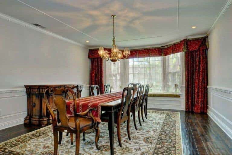 Large wooden table paired with wooden chairs on the rug. This room features hardwood flooring and a white wall with a large window and a pleasant curtain.