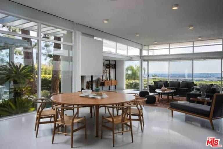 A modern house with a living space and dining area. The round wooden tables paired with wooden chairs, this room also features a glass wall and a great view outside.