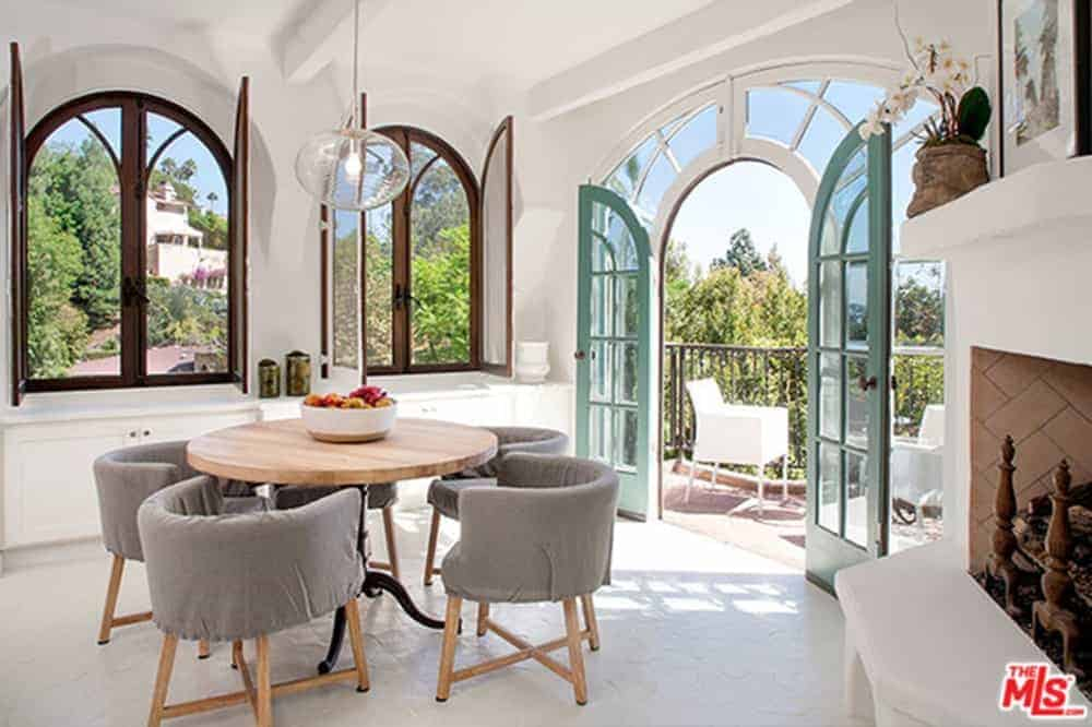 A small dining area with round wooden tables mixed with grey wooden chairs in front of large glass entryway leading to a small balcony. This room features a large window with a beautiful ambiance outside.