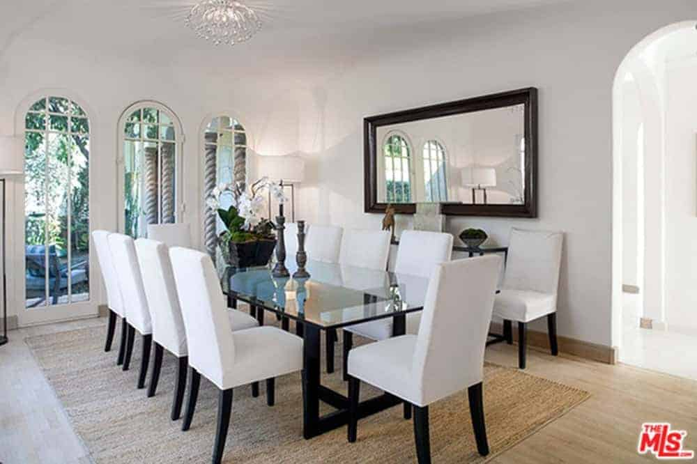 This white dining room featuring a large rectangular glass table paired with white chairs on the carpet. It also features a large window with a gorgeous garden outside.