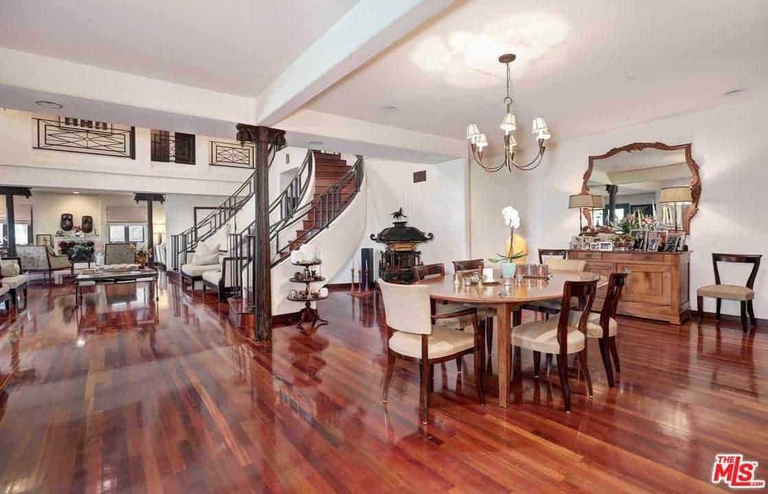 Large living space and dining area with gorgeous hardwood flooring and white walls. The round small wooden table paired with brown chairs lighted by the chandelier.