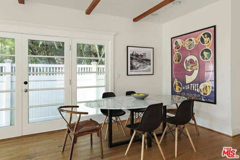 Small dining area featuring a glass oval table with modern chairs on stylish hardwood flooring. This area has a white ceiling with huge wall decors and a doorway leading to the terrace.