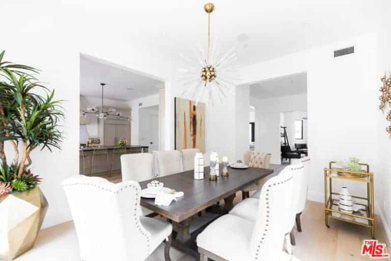 A large dining area features a wooden table mixed with modern white chairs. It also features a white wall and a white ceiling lighted by the modern chandelier.