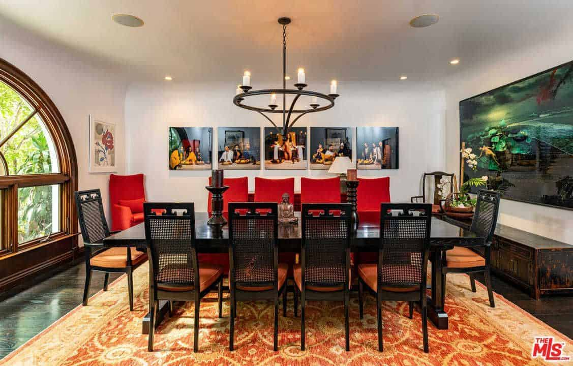 Full view of dining area featuring dark wooden tables and chairs on the rug. This room also features a white wall with multiple wall decor lighted by the gorgeous chandeliers.