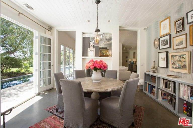 Small round dining table with grey chairs on the rug in front of the door with a great view outside.