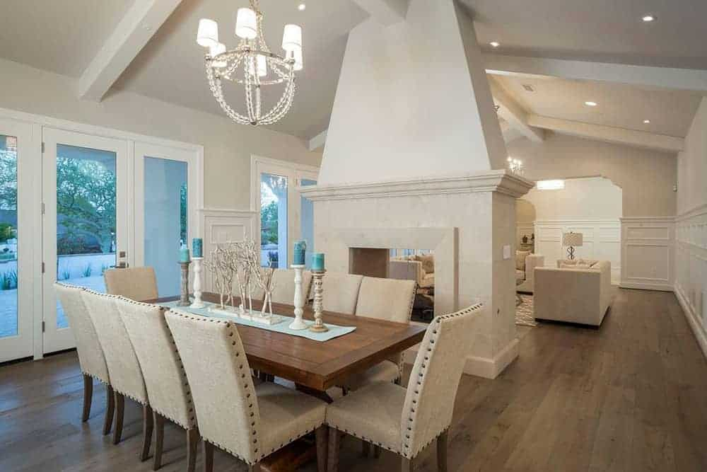 Classy dining area featuring wooden tables with brown chairs in front of the glass door with a beautiful view outside.