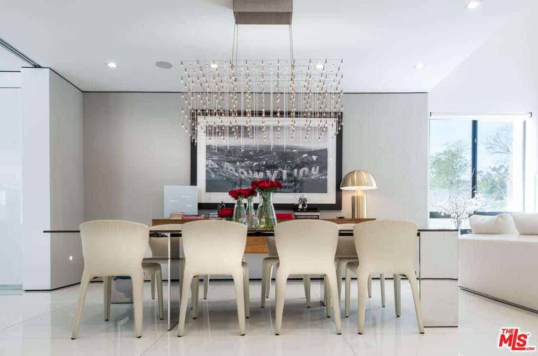 A classy dining area featuring an elegant dining table with white chairs lighted by the stunning chandelier. It also features white walls with huge wall decor.
