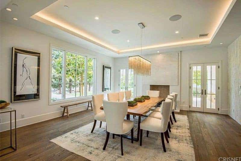 Large dining area featuring hardwood flooring and white walls with large windows and beautiful trees outside. The dining table set lighted by a stunning chandelier.