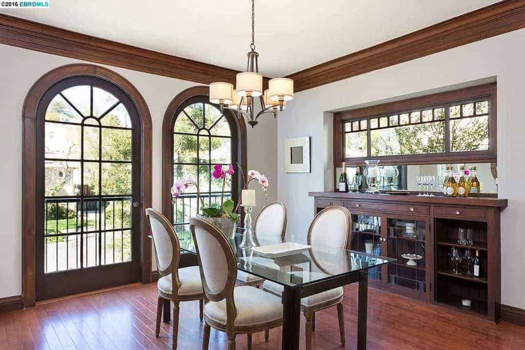 This dining room featuring white walls and hardwood flooring, along with a modern dining table set light by the attractive modern chandelier.